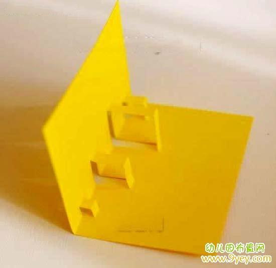 1. 首先准备两张黄色A4卡纸  2. 然后将纸张进行对折  3. 接着按照图示中的示意线在其中一张卡纸上绘制线条  4. 然后用剪刀对绘制好的线条进行剪裁  5.这个时候我们将其向内压进来,就可以形成如图所示的构型了  6. 接着制作一个气球小装饰和小丝带,这个气球小装饰非常容易制作,圆形的纸片粘贴到一起加上一些线条即可,这里就不做详细的说明了。