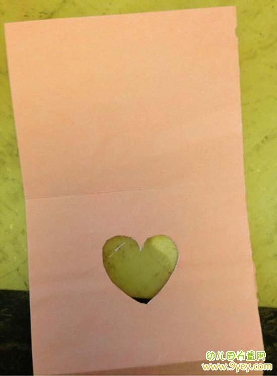 手工材料:白色卡紙、粉色卡紙、鉛筆、剪刀、膠水、小貼畫  1. 把白色卡紙對折  2. 把粉色卡紙剪成長方形,大小是白色卡紙的一半  3. 把粉色卡紙對折,兩頭各向內折一小部分  4. 在粉色卡紙的下半部分用鉛筆畫一個紅心  5. 用剪刀剪下紅心  6. 在另一白色卡紙上畫一個正方形并剪下來  7.